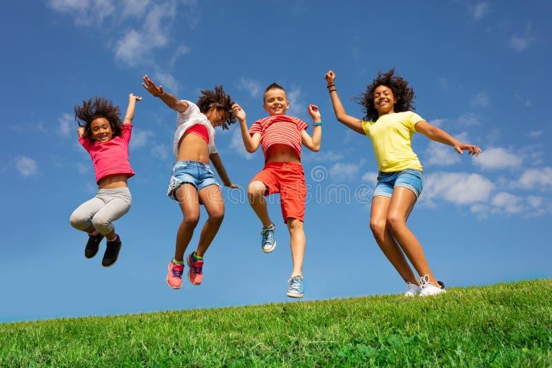 Tanz- und Springgruppe verschiedener Kinder auf Rasen lizenzfreie stockfotografie