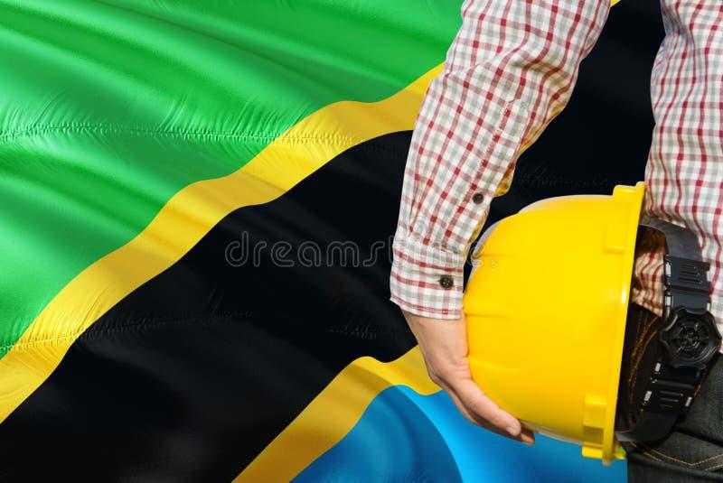 Tanzański inżynier trzyma żółtego zbawczego hełm z machać Tanzania chorągwianego tło Budowy i budynku poj?cie obrazy royalty free