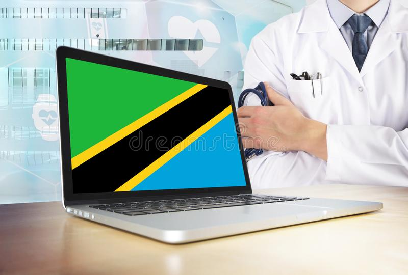 Tanzania healthcare system in tech theme. Tanzanian flag on computer screen. Doctor standing with stethoscope in hospital. Cryptocurrency and Blockchain stock images
