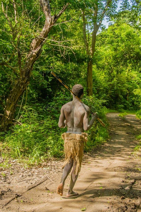 Tanzania - Tanzanian Bushman @ Selous Game Reserve. Original Tanzanian inhabitant or bushmen walking through the forest of Selous Game Reserve on a sunny early stock image