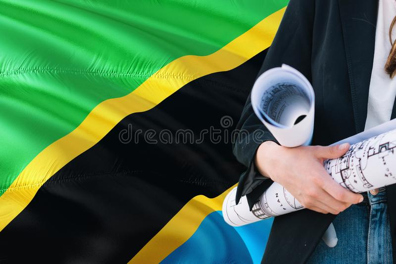 Tanzanian Architect woman holding blueprint against Tanzania waving flag background. Construction and architecture concept.  royalty free stock photo