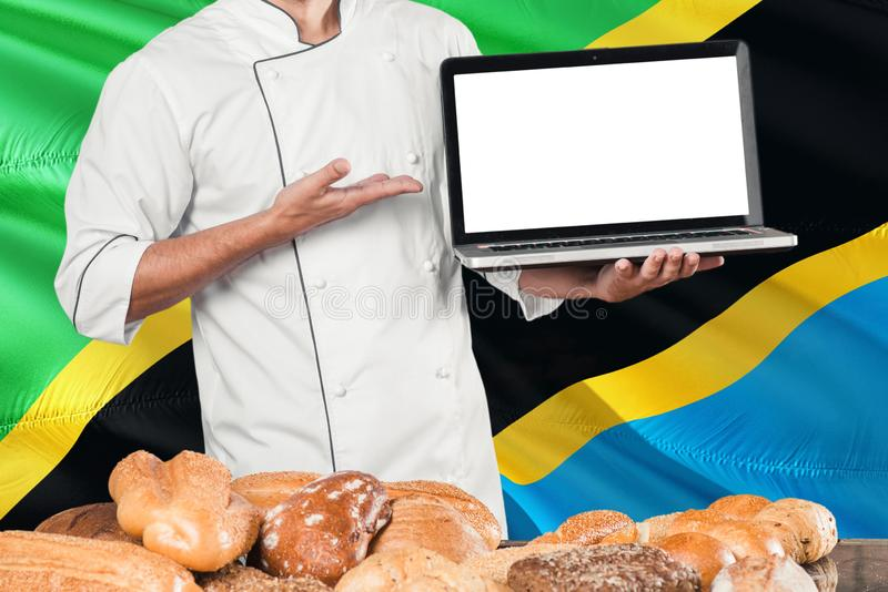 Tanzanian Baker holding laptop on Tanzania flag and breads background. Chef wearing uniform pointing blank screen for copy space.  royalty free stock photo