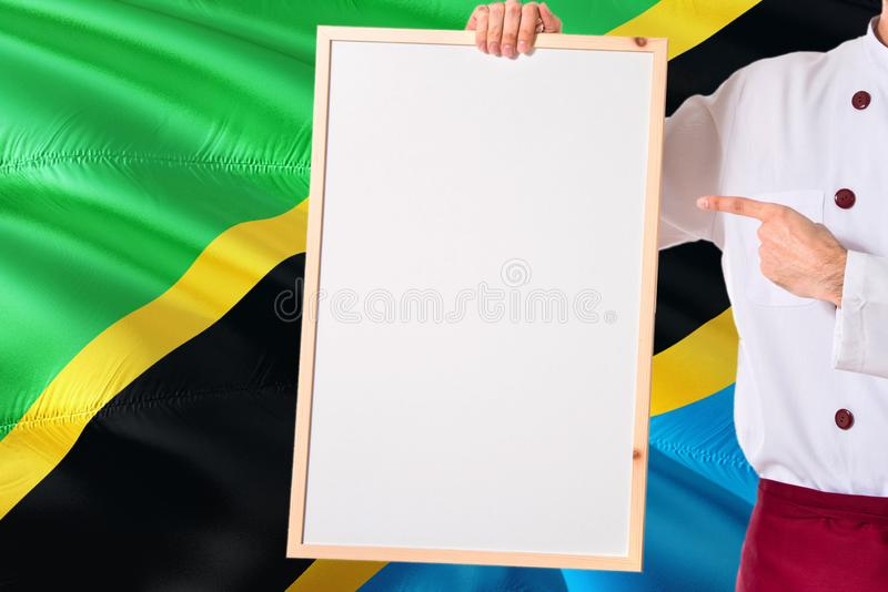 Tanzanian Chef holding blank whiteboard menu on Tanzania flag background. Cook wearing uniform pointing space for text.  royalty free stock image