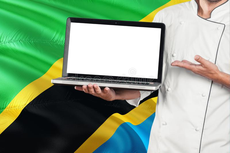 Tanzanian Chef holding laptop with blank screen on Tanzania flag background. Cook wearing uniform and pointing laptop for copy. Space royalty free stock photo