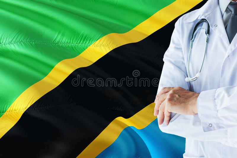 Tanzanian Doctor standing with stethoscope on Tanzania flag background. National healthcare system concept, medical theme.  stock image