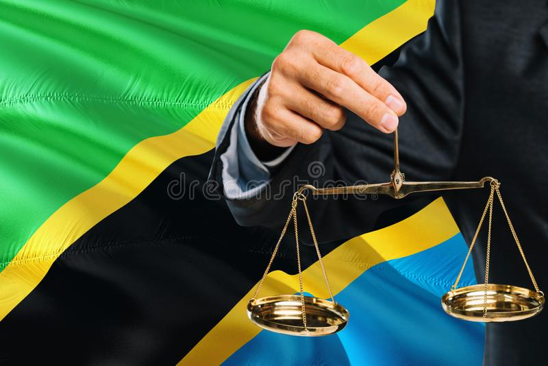 Tanzanian Judge is holding golden scales of justice with Tanzania waving flag background. Equality theme and legal concept.  stock photo