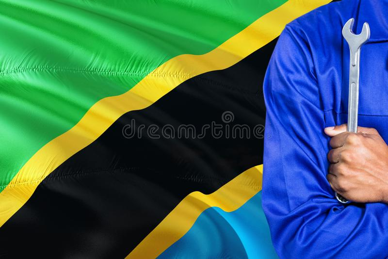 Tanzanian Mechanic in blue uniform is holding wrench against waving Tanzania flag background. Crossed arms technician.  royalty free stock photo