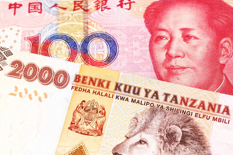 Tanzanian money with a Chinese yuan banknote in macro. An orange and white two thousand Tanzanian shilling note with a red Chinese, one hundred yuan renminbi royalty free stock image