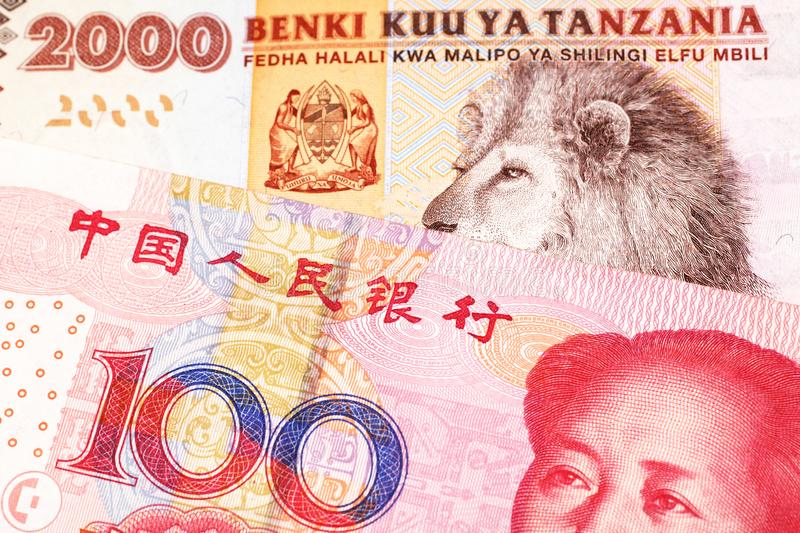 Tanzanian money with a Chinese yuan banknote in macro. An orange and white two thousand Tanzanian shilling note with a red Chinese, one hundred yuan renminbi stock photography