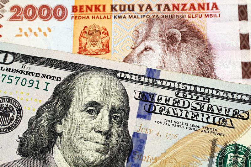 A Tanzanian shilling bank note with an American one hundred dollar bill. An orange and blue two thousand Tanzanian shilling bank note with a United States blue royalty free stock photos