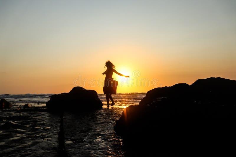 Tanzen auf einem Strand bei Sonnenuntergang lizenzfreies stockfoto