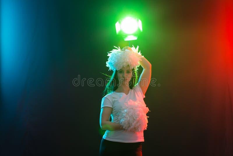 Tanzen, cheerleading und Leutekonzept - junges Mädchen in der Dunkelheit unter buntem Licht mit Pompoms auf ihrem Kopf lizenzfreies stockbild