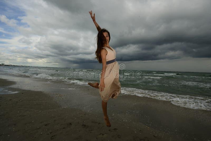 Tanzen der jungen Frau auf einem Strand stockfotos