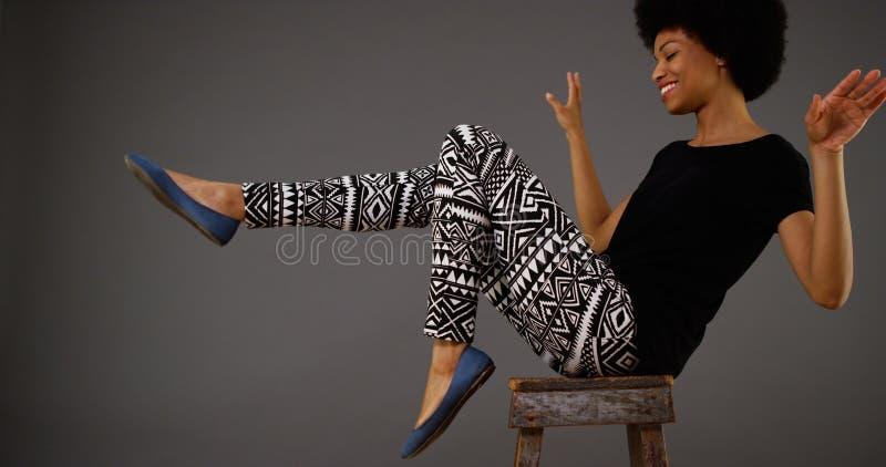 Tanzen der schwarzen Frau auf Stuhl stockbild
