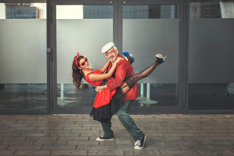 Tanzen des alten Mannes mit einer jungen Frau stockbild