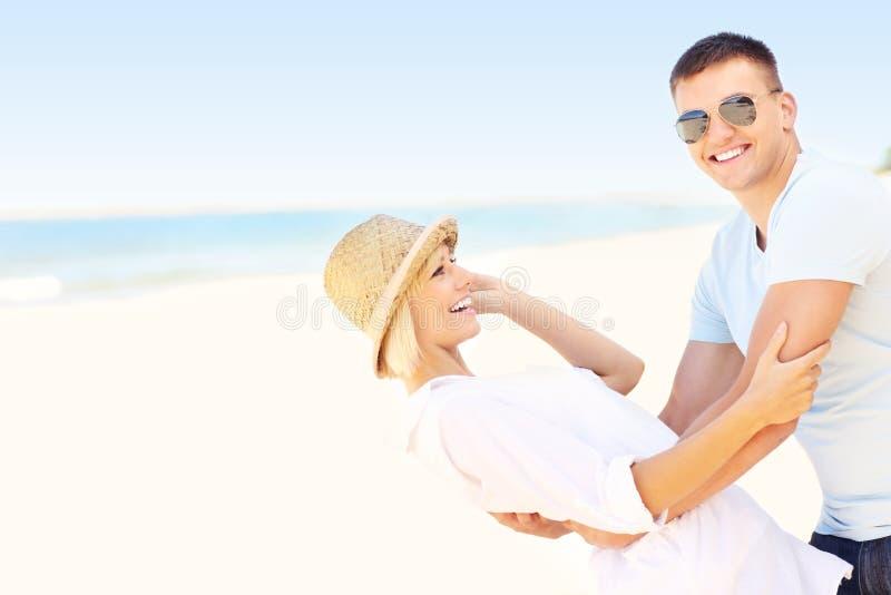 Tanzen des glücklichen Paars am Strand stockbilder