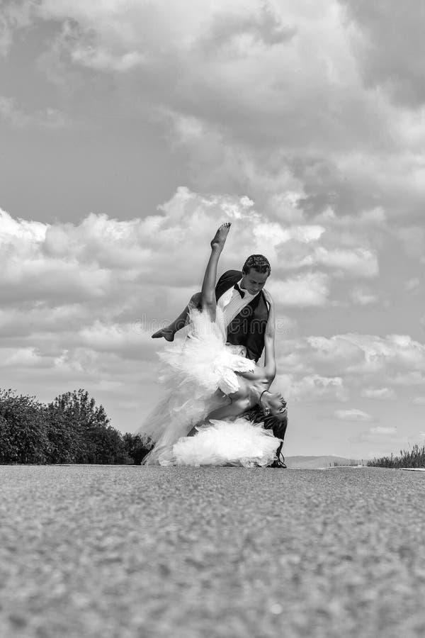 Tanzen des Hochzeitsglücklichen paars auf Straße lizenzfreies stockbild