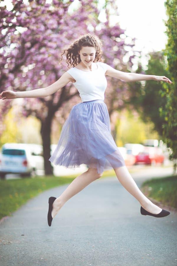 Tanzen des jungen Mädchens und Springen unter die blühenden Kirschblüte-Bäume lizenzfreie stockfotografie