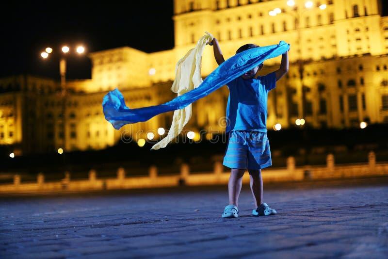 Tanzen des kleinen Jungen in der Nachtstadtansicht lizenzfreie stockfotografie