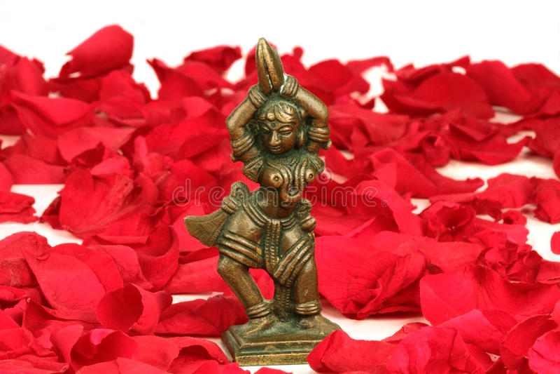 Tanzen Devi auf einem Bett der roten rosafarbenen Blumenblätter lizenzfreie stockfotografie