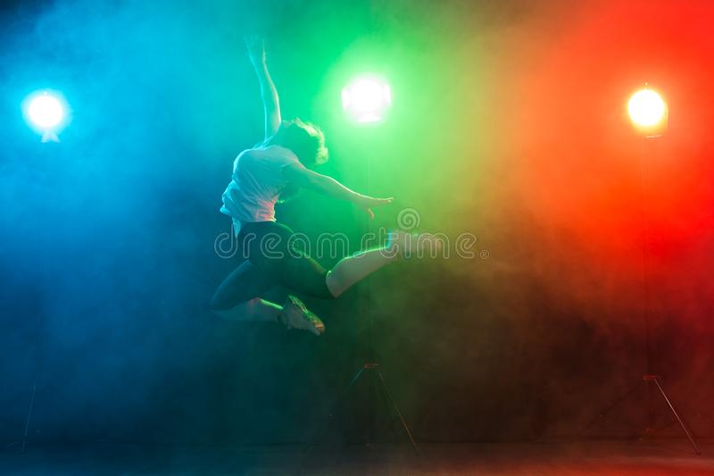 Tanzen, Sport, Jazzriesige angst und Leutekonzept - junge Frau springen in die Dunkelheit unter buntes Licht stockfotos