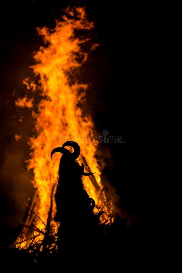 Tanzen um das enorme Ritualfeuer in der Maske mit Hörnern lizenzfreies stockfoto
