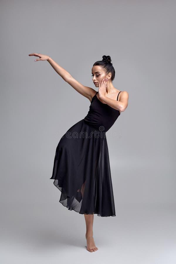 Tanzende Ballerina in einem schwarzen Kleid Zeitgen?ssische w?rdevolle Leistung auf einem grauen Hintergrund stockfotografie