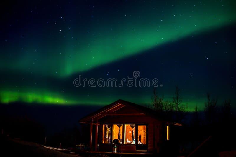 Tanzende Polarlichter, Bungalow der Vordergrund stockfotografie