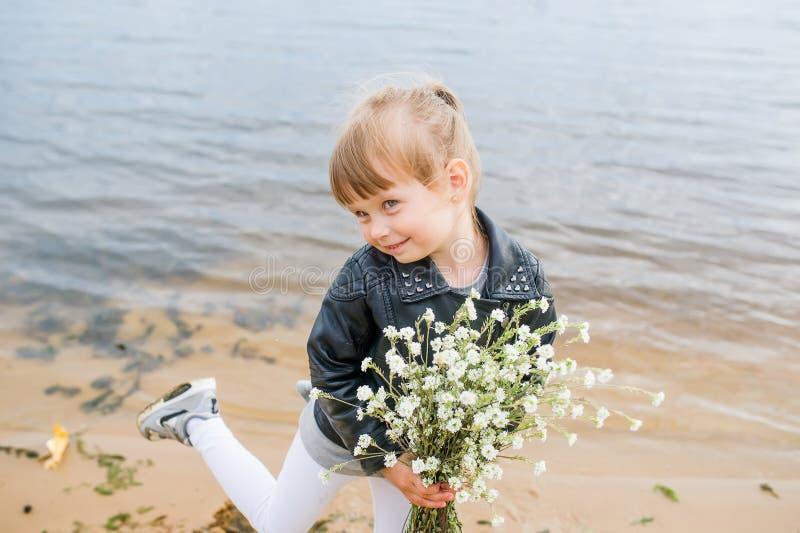 Tanzendes kaukasisches Mädchen in der Jacke, halten Wildflowers neben einem See in einem Park stockbild