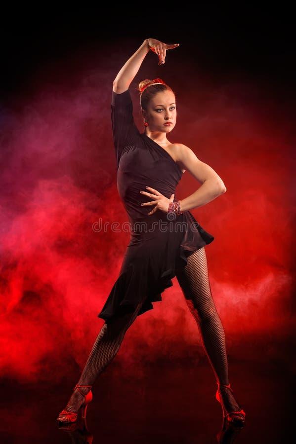 Tanzenflamenco der jungen Frau auf dunkelrotem Hintergrund lizenzfreie stockfotos
