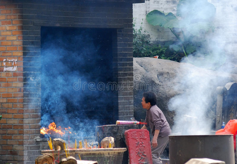 Taoist temple scene, Macao. An old lady is burning the hell money in a Taoist temple stock image