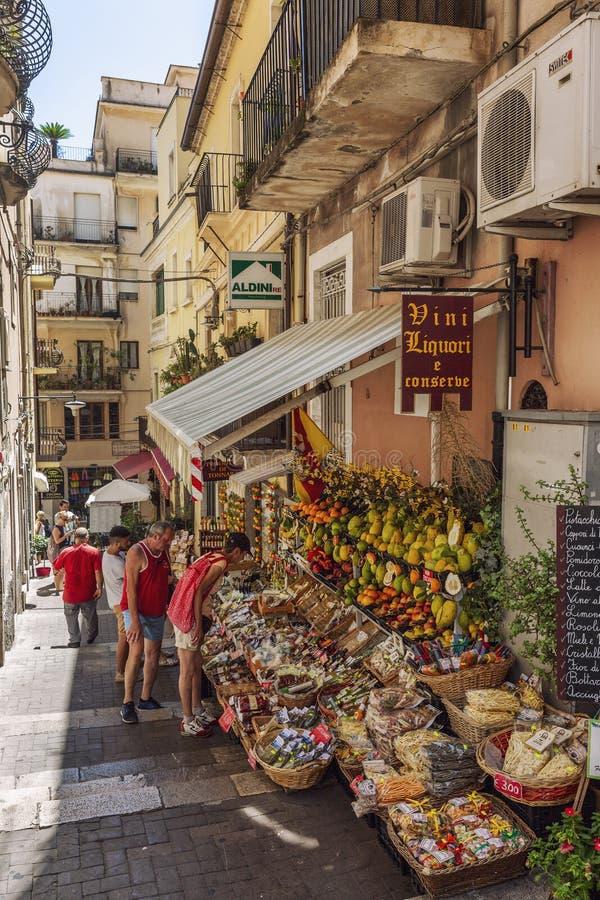 Taormina, Italia, 08/30/2016: Una calle estrecha en la ciudad vieja La gente compra frutas y recuerdos foto de archivo