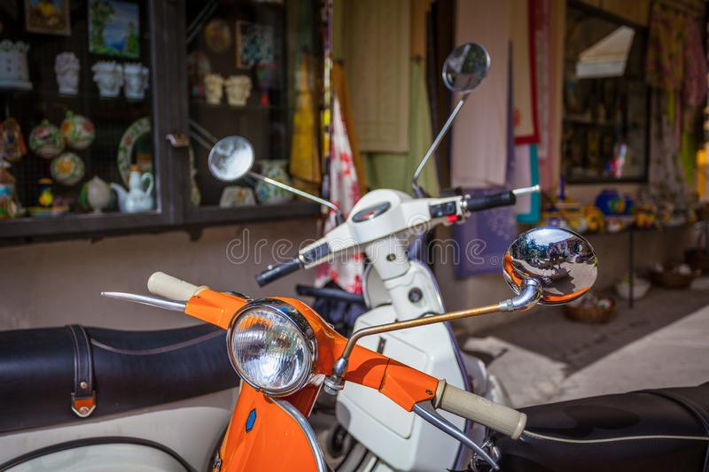 Classic Italian motorcycle bikes `Vespa` parked on the street royalty free stock photography