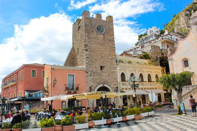 Taormina, Sicily, Italy - Apr 8th 2019: People sitting in outdoor restaurants and cafes on beautiful Piazza IX Aprile square. In front famous Clock Tower stock image