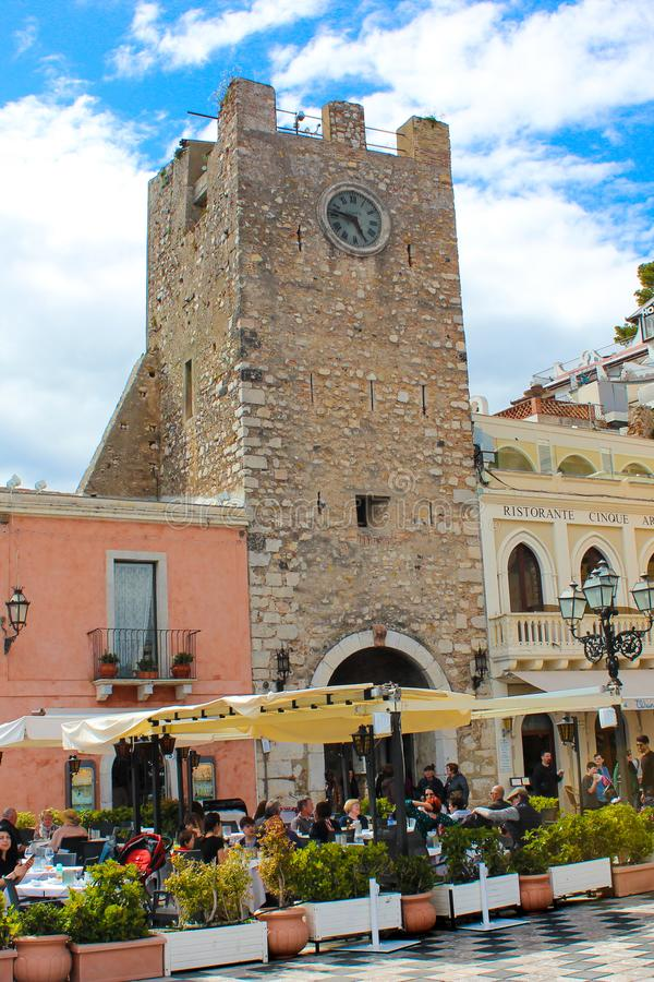 Taormina, Sicily, Italy - Apr 8th 2019: Tourists in restaurants and cafes gardens on historical Piazza IX Aprile square in front. Of famous Clock Tower royalty free stock images