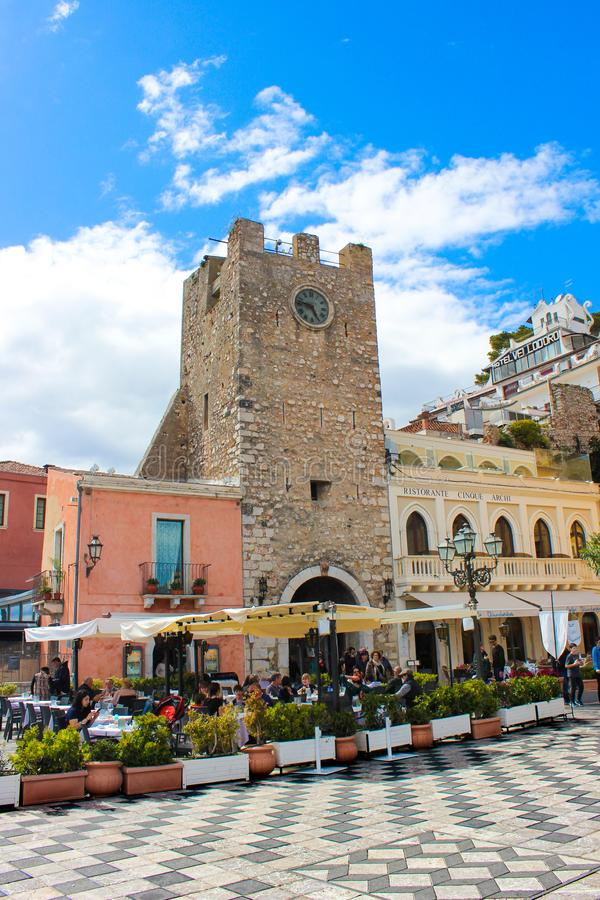 Taormina, Sicily, Italy - Apr 8th 2019: Tourists sitting in outdoor restaurants and cafe on Piazza IX Aprile square in front. Famous Clock Tower. The city is a stock images
