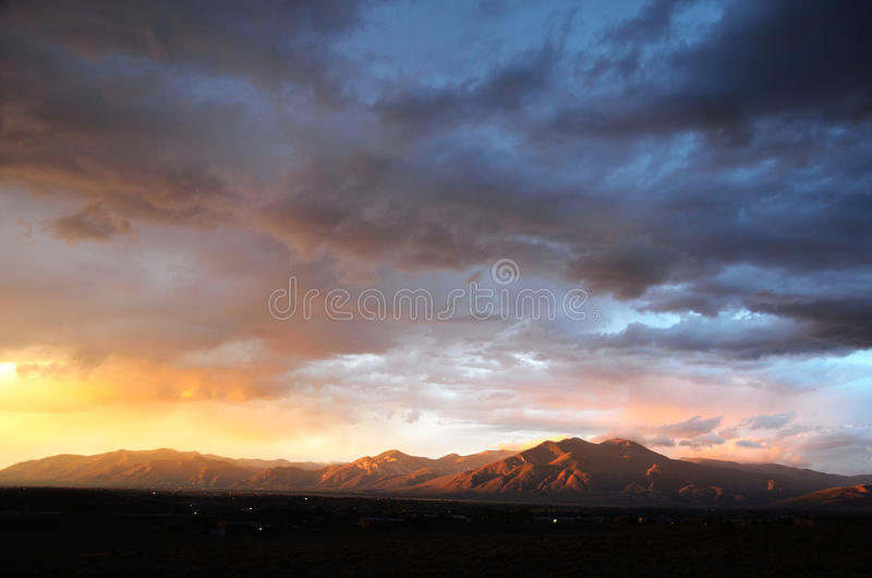 Taos Monsoon Sunset. The sunset reflects in the monsoon clouds above the Sangre de Christo Mountains at Taos, New Mexico royalty free stock photography