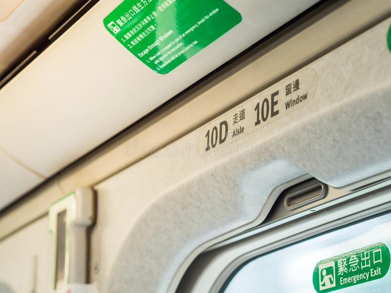 Closeup overhead seat numbers in Taiwan High Speed Rail THSR and Emergency Exit sign with yellow sunlight through the window. TAOYUAN, TAIWAN - March 11, 2019 stock image