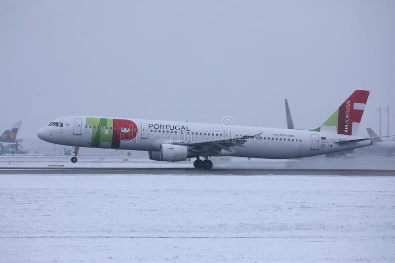 TAP Air Portugal plane taxiing on runway in Munich Airport, Germany, Winter time with snow. TAP Air Portugal plane getting ready to take off from Munich Airport stock image