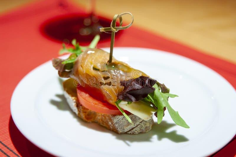 Tapa de Montadito de salmones, del rucula, del queso, de la lechuga, del lanzamiento del tomate en la rebanada de pan y del tema  fotografía de archivo libre de regalías