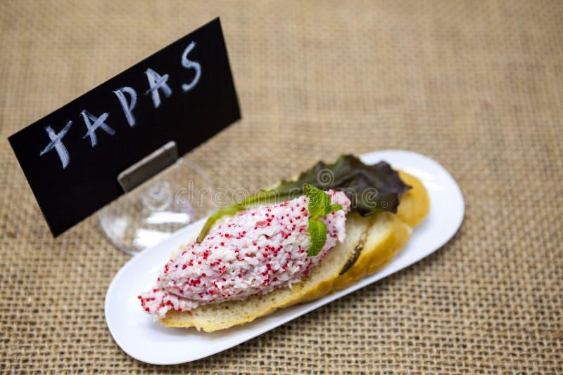 TAPAS-affiche Heerlijke Spaanse tapas met krab tartare met vliegende vissenkuiten en salade op een plak van baguette Een uitsteke royalty-vrije stock fotografie