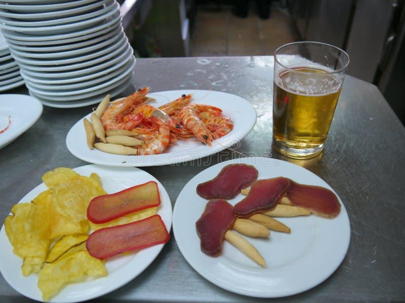 Tapas délicieux des plats blancs et d'un verre de bière images stock
