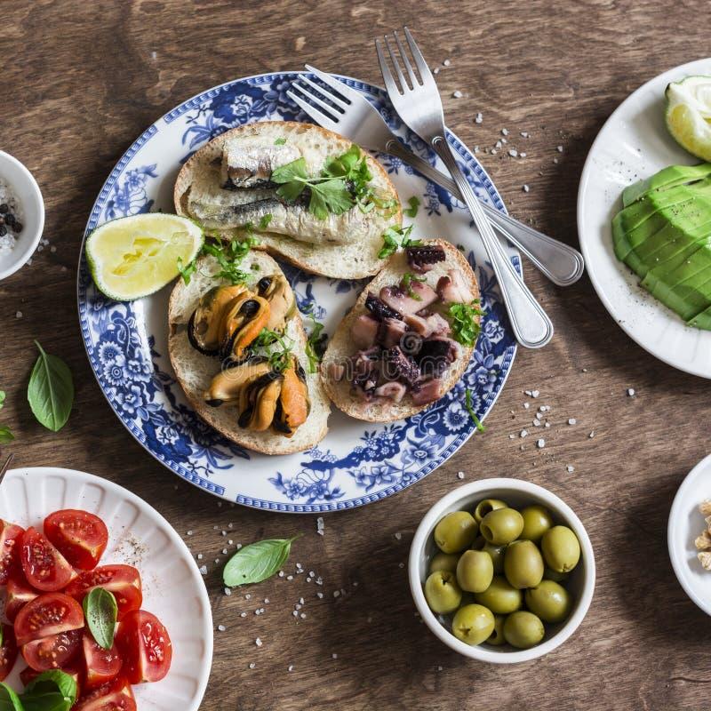 Download Tapas Délicieux - Sandwichs Avec Des Sardines, Des Moules, Le Poulpe, Le Raisin, La Tomate Et L'avocat Sur La Table En Bois Image stock - Image du dîner, délicieux: 87707515