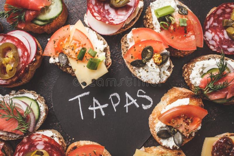 Tapas espagnols assortis avec les poissons, la saucisse, le fromage et les légumes Fond foncé, vue supérieure photographie stock libre de droits