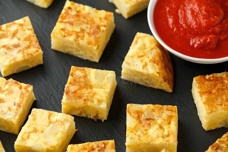 Tapas espagnols de Frittata de pomme de terre avec la sauce tomate sur le conseil en pierre photo libre de droits