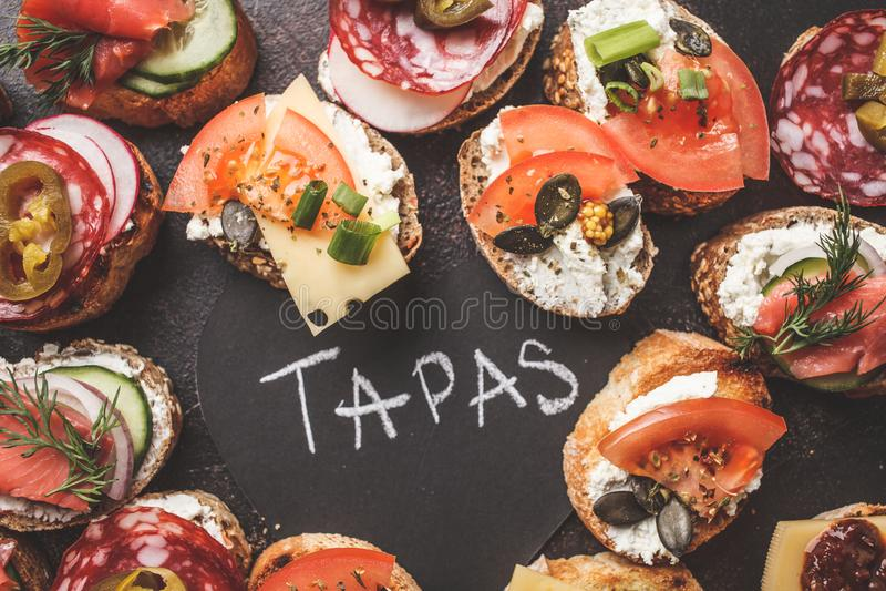 Tapas espanhóis classificados com peixes, salsicha, queijo e vegetais Fundo escuro, vista superior fotografia de stock royalty free