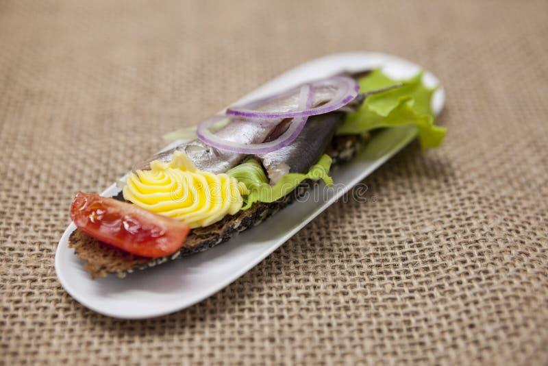 Tapas espanhóis deliciosos com o arenque pequeno da salada da manteiga e da cebola, atlântico no baguette da fatia Um fundo excel imagem de stock