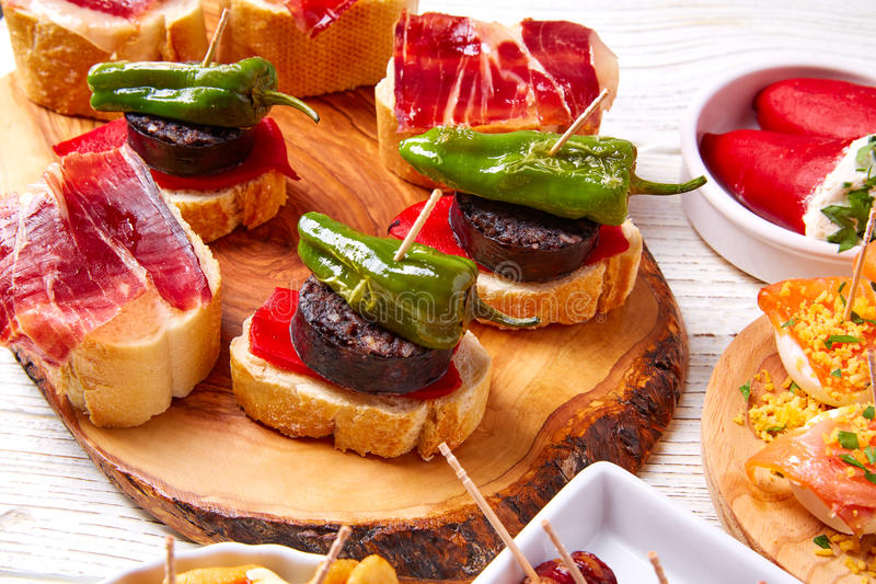 Tapas mix and pinchos food from Spain recipes also pintxos. On a white wood board stock images
