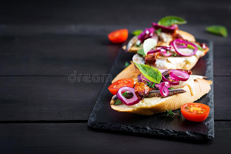 Tapas - Spanish bar food. Bruschetta with slices of sun-dried tomatoes,cheese mozzarella and anchovies. On dark background stock photo