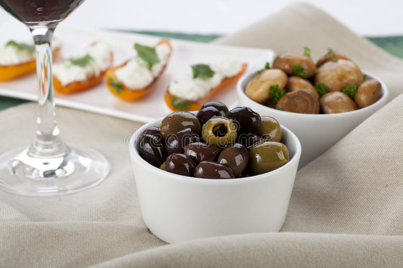 Tapas Time. Tapas spread with olives, marinated mushrooms and cheese filled peppers stock image